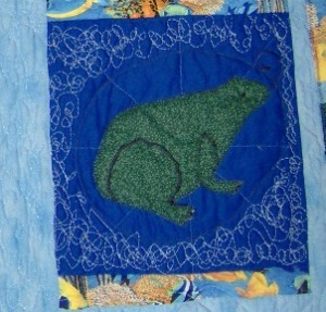 The frog block. The frog is one piece, the legs are defined with zig zag stitching. The swirling water around the frog is just my  unusual quilting.
